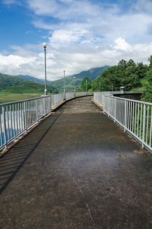 pathway on top of dam for overlooking the water and mountains photo