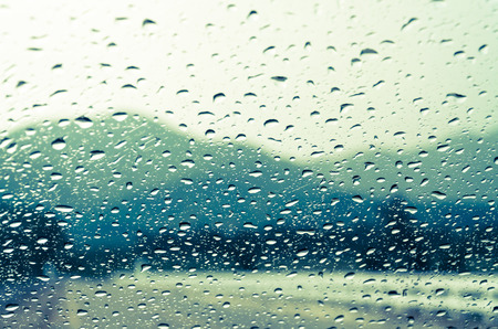 auto glass: raindrops on auto glass with mountain view in vintage style