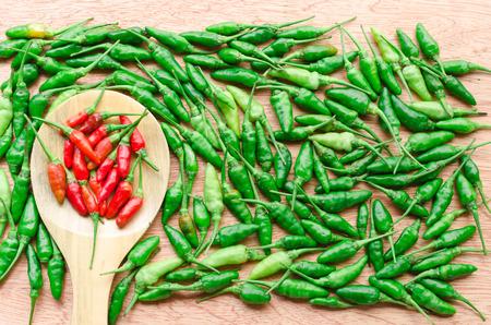 spur: Cayenne pepper, chili spur pepper, long fed pepper, spur pepper,Chilli Padi, Birds Eye Chilli, Bird Chilli or Thai pepper on wood texture Stock Photo