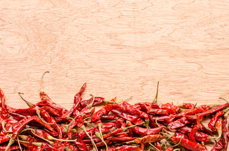 crushed red peppers: red dried chili pepper on wood background