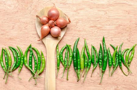padi: shallot on wooden spoon and green chili Stock Photo