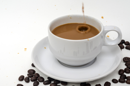 shape cub: coffee in white cup with coffee beans and coffee stain