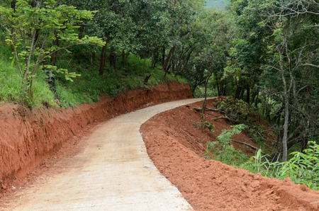 clay stone road in jungle: road construction in the forest with red earth