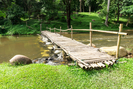 wooden bridge: Old wooden bridge over the stream with green lawn