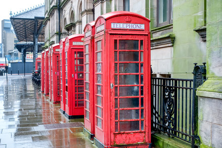 a row of red telephone boxes on a wet afternoon