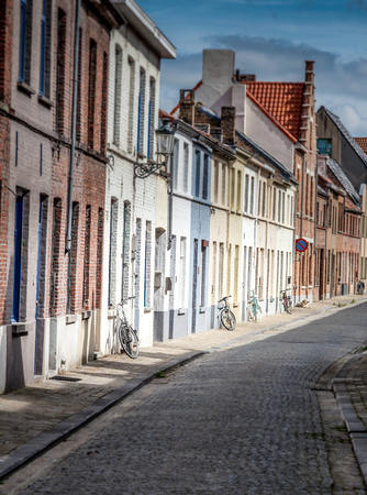 5 bicycles lean against houses in a strret in Bruges, Belgium Stock Photo