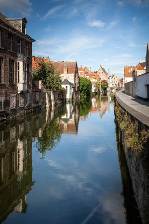 a canal in bruges on a bright sunny day Imagens