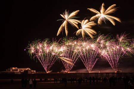silhoutted: fireworks light of the sky, people silhoutted on the beach Stock Photo