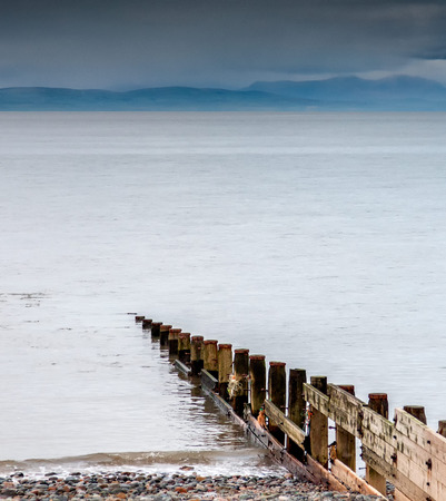 groyne: Incoming tide starts to cover a groyne on Rossal point beach, lancashire UK
