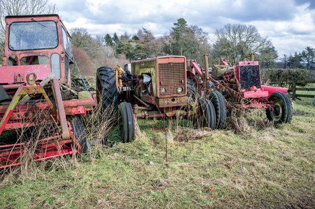 3 old decrepit tractors lie neglected  in a field