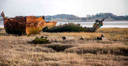 boat wrecks lie rotting away on the marshes of the river Wyre estuary