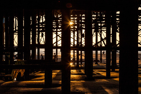 struts: people in silhouette under the pier Stock Photo