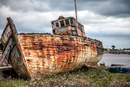 a boat lies abandoned rotting away