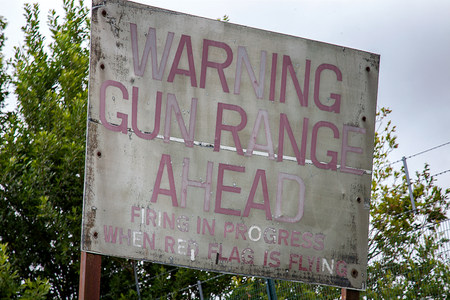 an old decaying sign warns of a firing range
