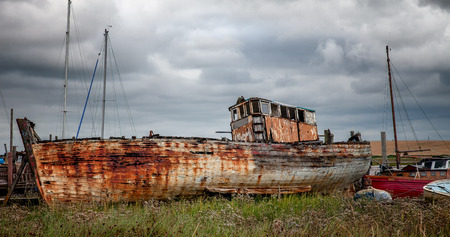 an old boat lies rotting away