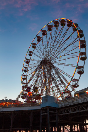 a view of a Ferris wheel as light begins to fade and the lights on the wheel become more prominent Imagens
