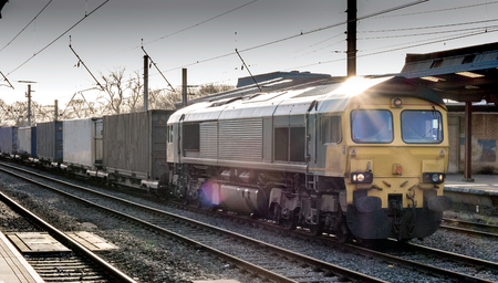 Freight train, at the station, sunlight reflecting off its roof