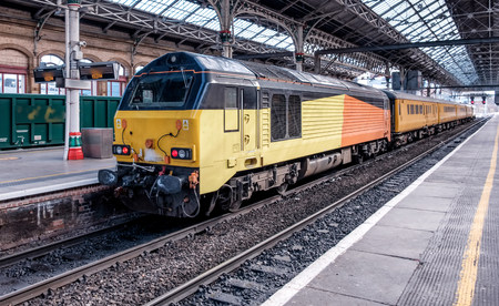 An engineering train pulled by a black, orange and yellow locomotive Editorial