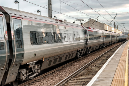 A high speed passenger train with a chemical plat reflected in its surface Imagens