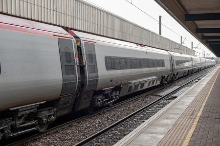 A highspeed passenger train stands at the platform in the rain