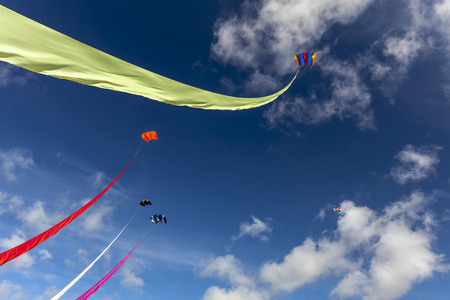 5 Kites flying high in a blue summers day sky