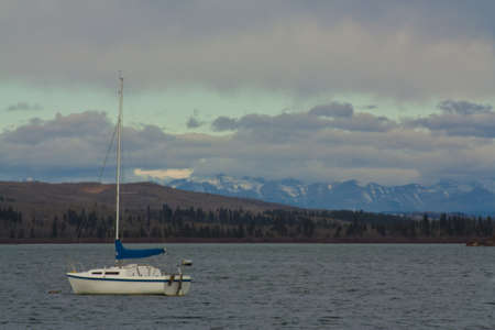 A lone sail boat anchored in a storm