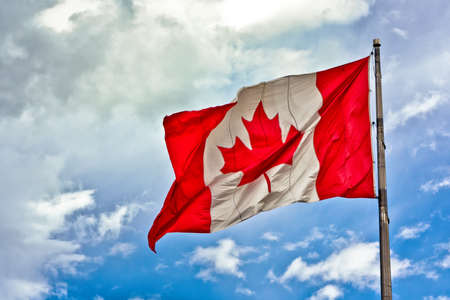 Canada flag flying in the wind on a sunny but cloudy day. photo