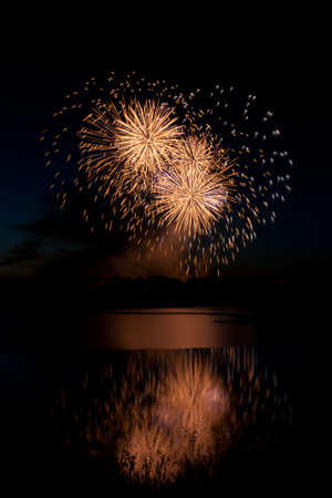 Heart shaped fireworks reflected on water. Stock Photo