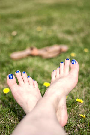 Crossed bare feet relaxing in dandelion spotted grass