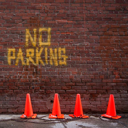 Brick wall with no parking written on it.  Orange pylons chained together are in front of the wall. photo