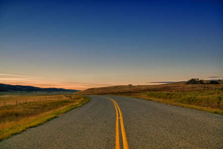 Landscape of a curved country road at sunset  photo