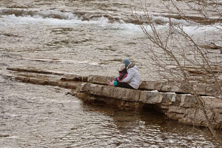 Woman and child sitting on rocks at the river in winter  Stock Photo - 15524774