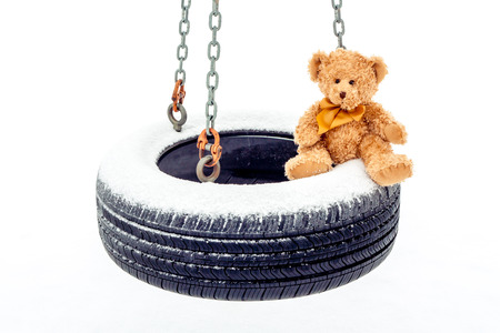 A stuffed bear sitting on snow covered tire swing. Stock Photo