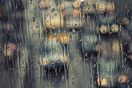 Traffic bokeh through a rain streaked window. Stock Photo