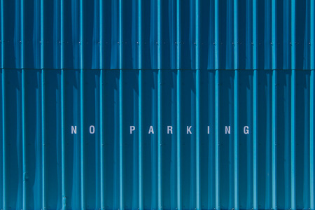 No parking printed on blue siding. Stock Photo
