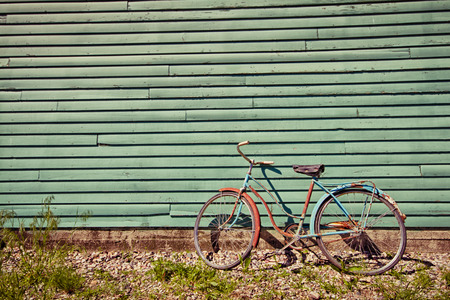 Abandoned bike leaning against a green wall.