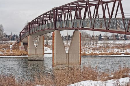 pedestrian bridge: Trestle pedestrian bridge in winter with a hooded photographer. Stock Photo