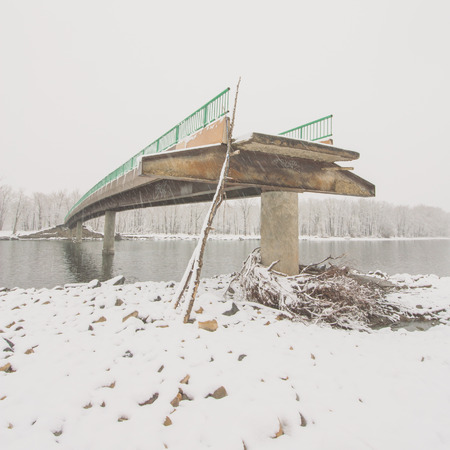 angled view: Square landscape of an angled view of a flood damaged bridge in winter.