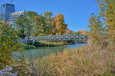 pedestrian bridge: Autumn landscape of a pedestrian bridge in Princes Island Park, Calgary, Alberta.
