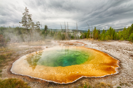 Landscape of a storm rolling over the Morning Glory Pool at Yellowstone National Park, Wyoming.