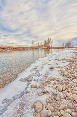 Winter landscape of the rocky snow framed river bank of  the Bow River, Alberta, Canada