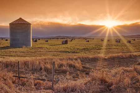 Landscape of the setting sun on the prairie with a grain elevator and sunburst. Stock Photo