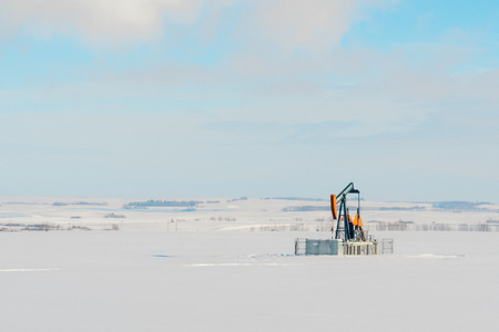 Landscape of a lone orange pumpjack in a snow covered field.