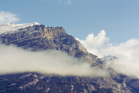 Close up of the snow capped peak of Grotto Mountain with a cloud. Stock Photo
