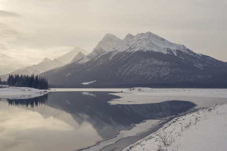canmore: Rocky Mountain landscape in winter with reflections in Goat Pond. Stock Photo