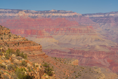 Landscape of the Grand Canyon with desert rock in the foreground.