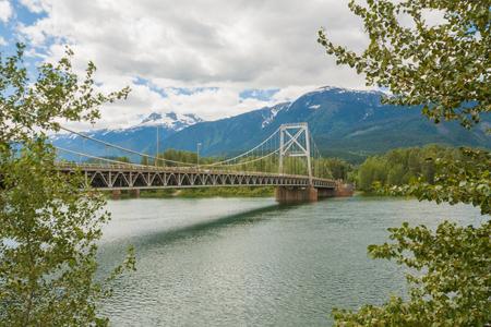 Landscape of the tree framed Revelstoke Bridge across the Columbia River. Stock Photo