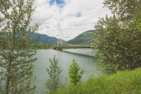 Revelstoke Bridge over the Columbia River, framed in trees and grass. Stock Photo