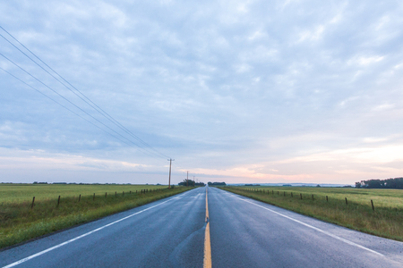 Landscape of a paved road in the prairie at dusk with an overcast sky.