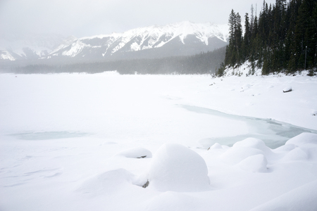 Winter Kananaskis Lake Landscape with snowy rock formation in the foreground. Stock Photo